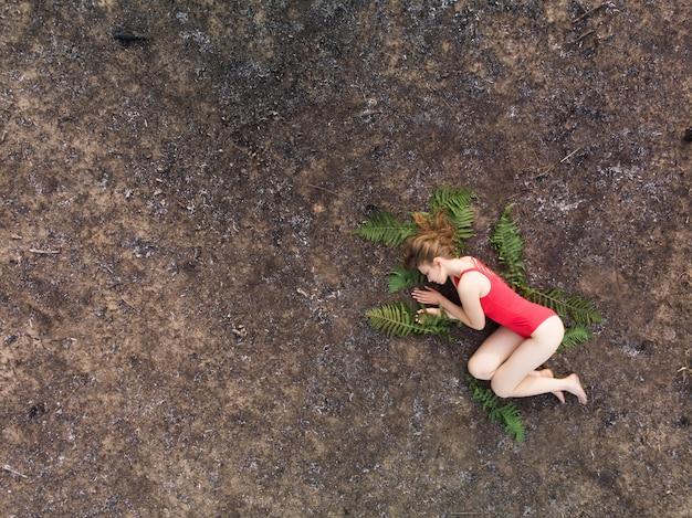 Женщина лежит на листьях папоротника на обожженной земле