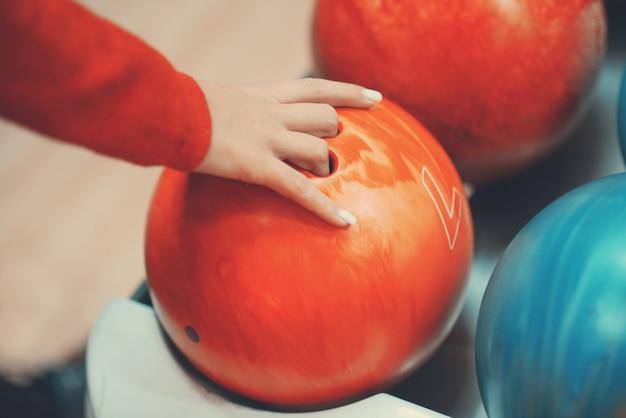 女性の手とボウリングのボール