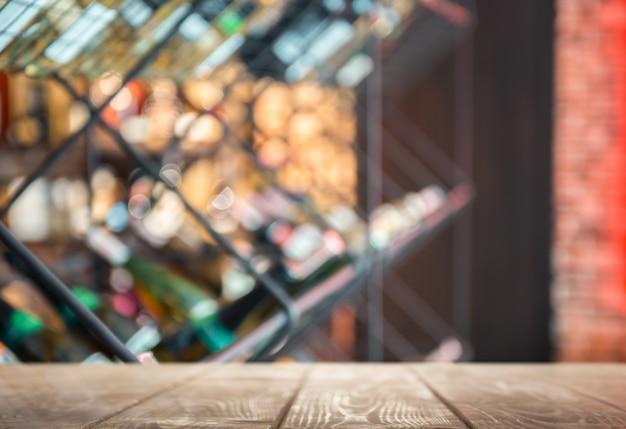 ぼやけたワイン店の背景を持つ木製のテーブルの製品プレゼンテーション