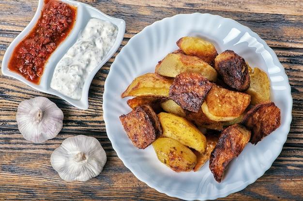Картофельные дольки с соусом и чесноком