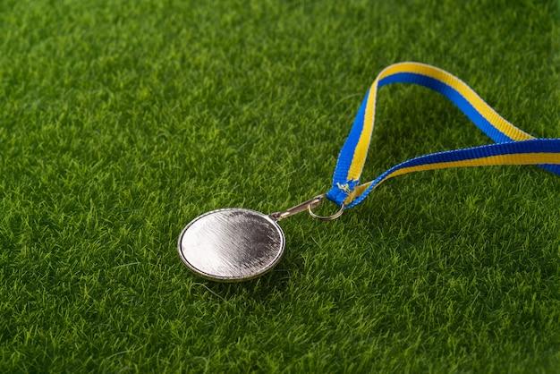 Золотая медаль на траве вид сверху