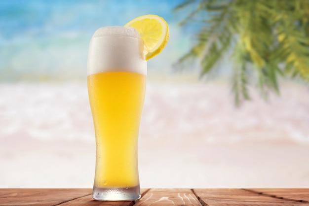 海とヤシの木の背景にレモンとビールのグラス
