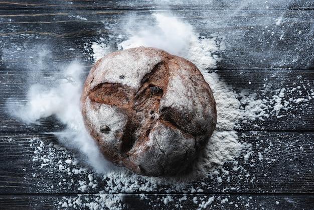 Круглый ржаной хлеб с мукой на черном столе, вид сверху