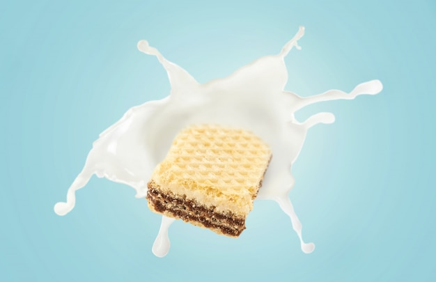 青色の背景に牛乳のスプラッシュとウェーハ