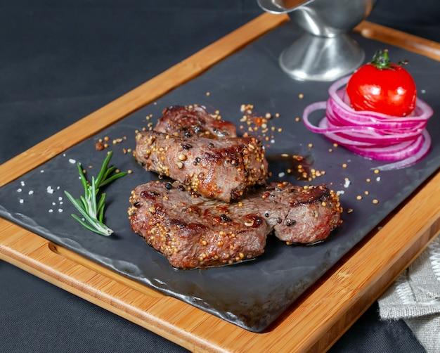 サービングプレートの食欲をそそる肉の部分は、暗闇の中でグリルトマトと新鮮な玉ねぎを添えてください。