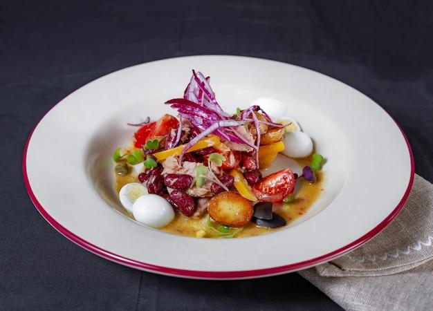 暗闇の中で皿に鶏肉、小豆、新じゃがいも、ウズラの卵のサラダ