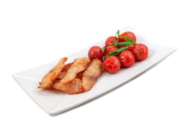 Жареная на гриле скумбрия с помидорами на белой тарелке, вид сбоку