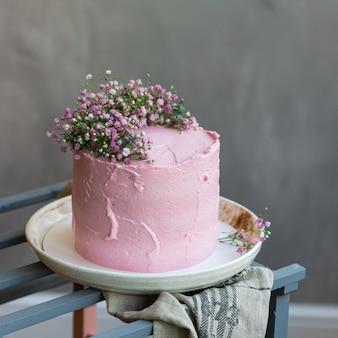 Фон с розовым кремовым тортом, украшенным мелкими цветами, серой скатертью и столом в скандинавском стиле