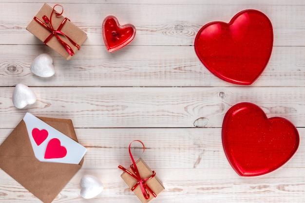 Творческая композиция на день святого валентина, белый деревянный фон с подарками, красные сердца, свечи, конверты, концепция дня святого валентина, плоская планировка, вид сверху, копия пространства