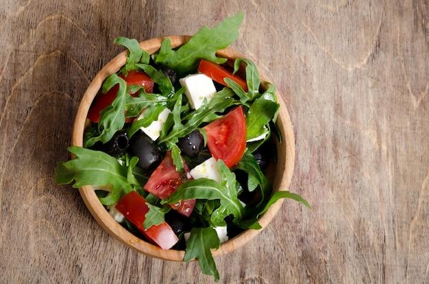 トマトとオリーブの木製の背景のサラダ