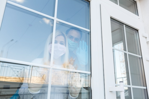 コロナウイルス。窓から見ている保護マスクを身に着けている病気の女性。感染を防ぐために患者を家に隔離した。病院の検疫室。黒と白の写真。