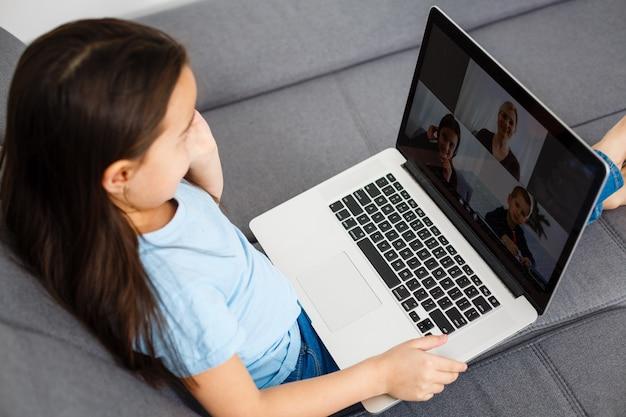 ノートパソコンでビデオ通話をする少女