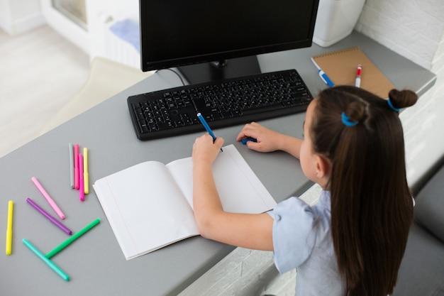 Довольно стильная школьница изучает домашнюю математику во время своего онлайн-урока дома, социальную дистанцию во время карантина, самоизоляцию, онлайн-концепцию образования, школьника