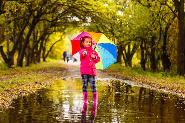 Очаровательны малыш девушка с красочными зонтик на улице в осенний дождливый день