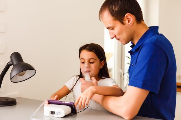 自宅でネブライザーで吸入を行う幼児少女。父親がデバイスを手伝って保持しています。インフルエンザ、咳、気管支炎の子供。ぜんそく吸入器吸入蒸気病気の概念