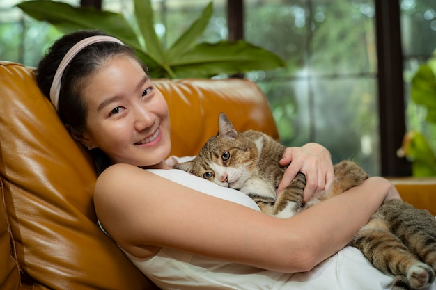 Азиатский женский домашний карантин с кошкой на диване