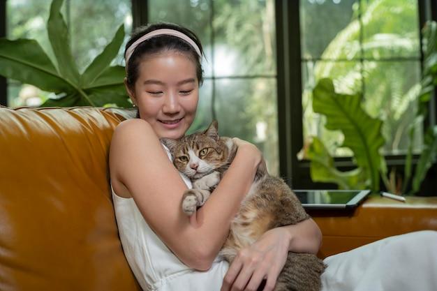 Азиатская женщина и кошка на диване