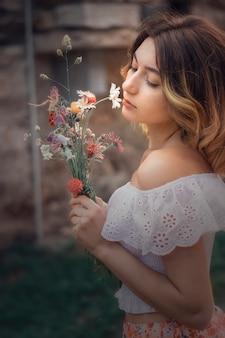 花を持つ美しい金髪の女性の肖像画