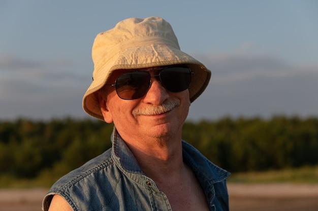 Пожилой мужчина в панаме у моря