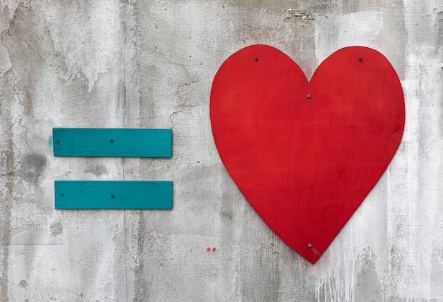 Синий знак равенства и красное деревянное сердце