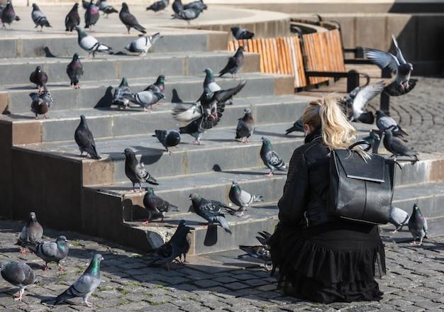 Молодая женщина кормит голубей