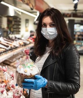 若い女性はイースターのパンを買う