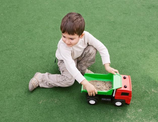 男の子はおもちゃの車で遊ぶ