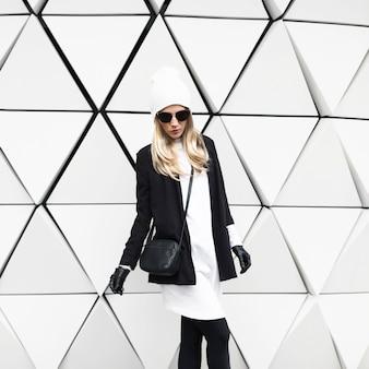 Гламурная блондинка стоит у стены. городская мода черно-белый стиль