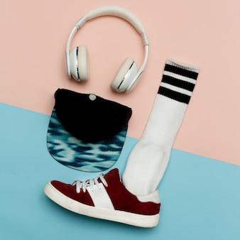 フラット横たわっていたファッションセット:ファッションスケートボードの靴、ファッションストッキング。キャップとヘッドフォン。最小限のアーバンミュージックスタイル。上面図。