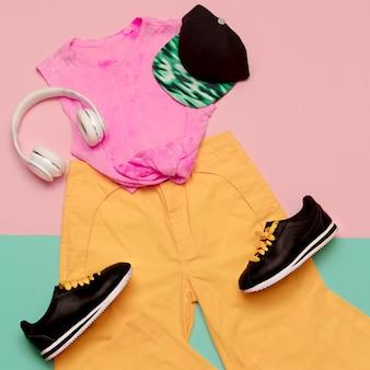 フラット横たわっていたファッションスポーツ服セット:靴スニーカー、ズボン、トップの明るい背景。アクセサリーキャップとヘッドフォン。都会的なスタイル。上面図。