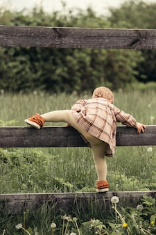 Ребенок лезет через забор в саду