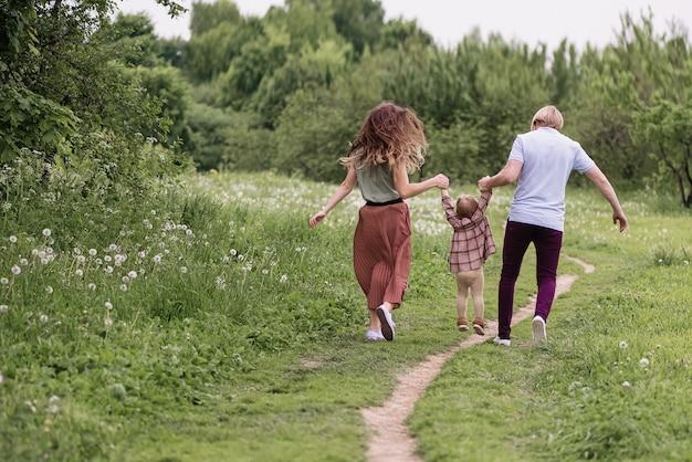 Счастливая семья гуляет с ребенком в парке летом