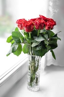 Букет из свежих красных роз в вазе стоит на подоконнике