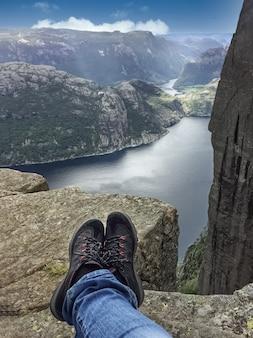 高い山の崖の上に座って、山頂からノルウェーのフィヨルドの景色を楽しんでいる旅行者の足
