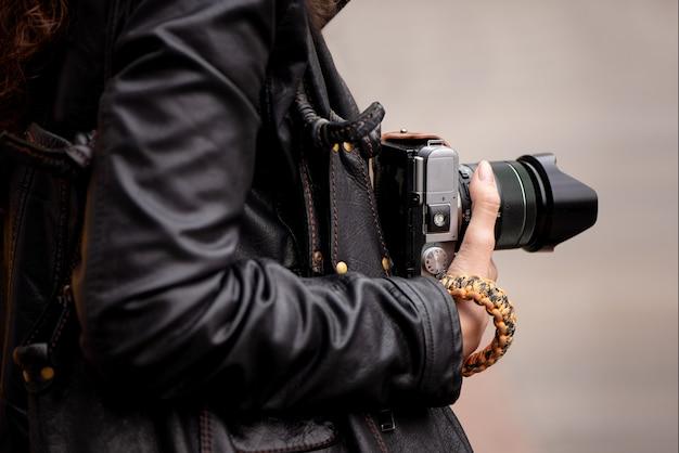 写真家がカメラを持って通りで写真を撮る