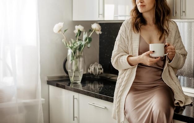 白いモダンなインテリアのキッチンルームでホットコーヒーのカップを保持している卓上に座っている若い魅力的な女性