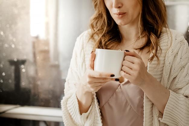 ホットコーヒーのカップを保持している若い魅力的な女性のショットを閉じる