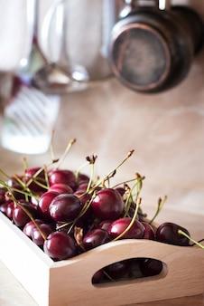 Коробка со спелой вишней в кухонном столе