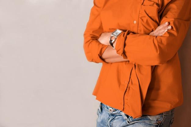 組んだ腕で壁の近くに立っている女性