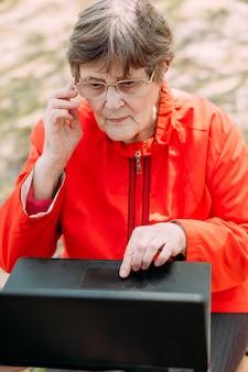 幸せな高齢の祖母が外でラップトップ通信を使用します