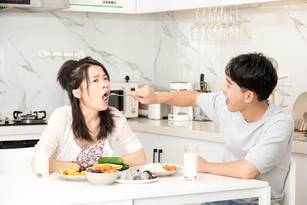 若いカップルは家で朝食をとる