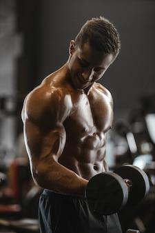 筋肉トレーニングフィットネスとボディービルの概念の背景-筋肉胴ビルダーフィットネス男性ジムの裸の胴体で腕腹筋背中のエクササイズを汲み上げてハンサムな強い運動男