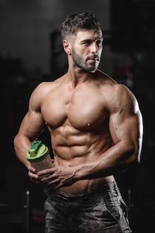 トレーニング後のボディービルダー飲料水。スポーツ筋肉フィットネスクロスフィットネスとボディービルのコンセプトジム背景腹筋運動ジム裸の胴体フィットネスコンセプト