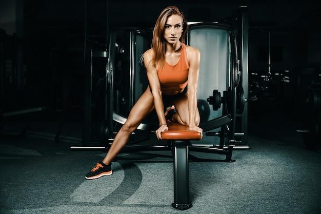 ジムで筋肉トレーニングをポンピングフィットネス女性