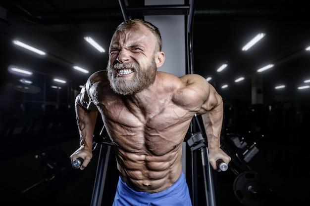 ボディービルダーが胸の筋肉の腕立て伏せバーを汲み上げる
