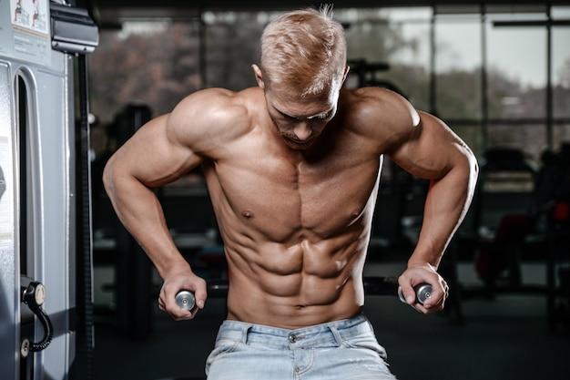 Сильный и красивый спортивный молодой человек мышцы пресса и бицепса