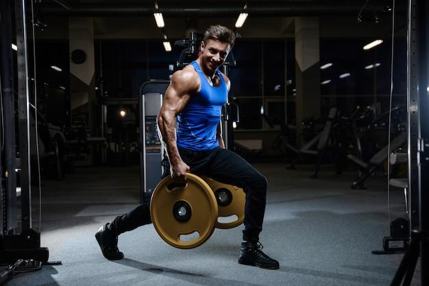 Красивая модельная разминка молодого человека в спортзале