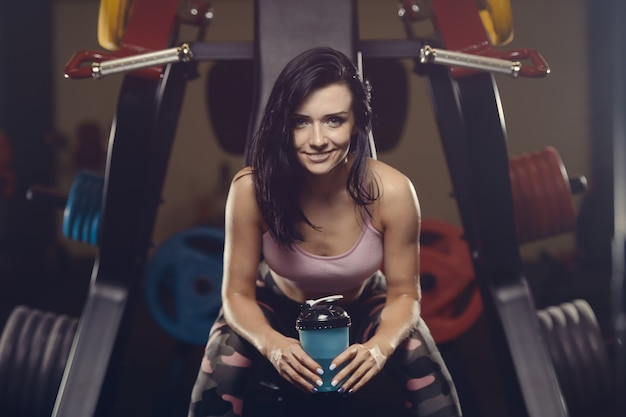Красивая спортивная молодая женщина, тренируясь в тренажерном зале