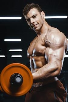 ハンサムな強い運動男性の筋肉トレーニングバーベルカールボディービルコンセプトをポンプ