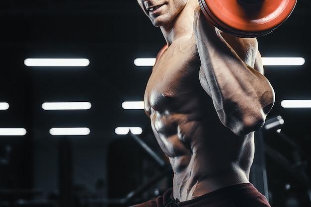 ハンサムな強い運動男性の筋肉トレーニングトレーニングバーベルスクワットボディービルコンセプト